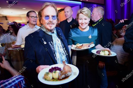 German singer and actor Frank Zander (2-L), German Minister for Family, Senior Citizens, Women and Youth Franziska Giffey (R) and  Governing Mayor of Berlin, Michael Mueller (L) serve dinner to homeless people during his annual Christmas party, in Berlin, Germany, 20 December 2019. Zander held the Christmas party for about 3,000 homeless people for the 25th time.