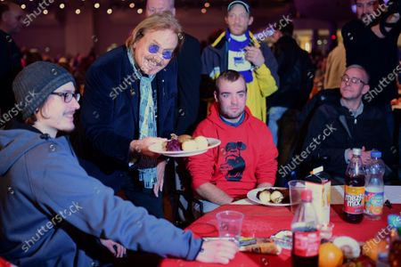 German singer and actor Frank Zander (2-L) serves dinner to homeless people during his annual Christmas party, in Berlin, Germany, 20 December 2019. Zander held the Christmas party for about 3,000 homeless people for the 25th time.