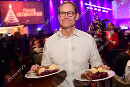 Berlin's Governing Mayor Michael Mueller serves dinner to homeless people during the annual Christmas party of German singer and actor Frank Zander (unseen) in Berlin, Germany, 20 December 2019. Zander held the Christmas party for about 3,000 homeless people for the 25th time.