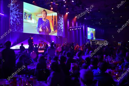 Stock Photo of A greeting of German Chancellor Angela Merkel is displayed on a giant screen at the dinner to homeless people during the annual Christmas party of German singer and actor Frank Zander in Berlin, Germany, 20 December 2019. Zander held the Christmas party for about 3,000 homeless people for the 25th time.