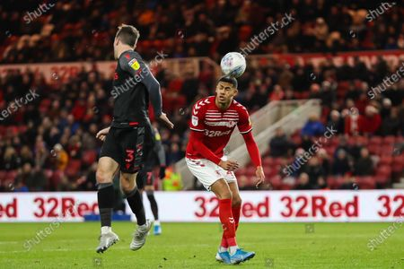 The lball inadvertently lands on the head of Middlesbrough forward Ashley Fletcher (11) after going over Stoke City defender Stephen Ward (3) during the EFL Sky Bet Championship match between Middlesbrough and Stoke City at the Riverside Stadium, Middlesbrough