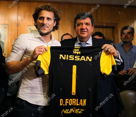 The former soccer player and new coach of the Uruguayan Penarol, Diego Forlan (L), receives the team's shirt from the club's President, Jorge Barrera (R) in Montevideo, Uruguay, 20 December 2019.