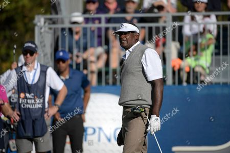 Qass Singh, center, watches after his father Vijay Singh, of Fiji Islands, hit his tee shot on the first hole during the first round of the Father Son Challenge golf tournament, in Orlando, Fla