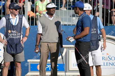 Vijay Singh, center, of Fiji Islands, talks with his son Qass Singh, right, before hitting their tee shots on the first hole during the first round of the Father Son Challenge golf tournament, in Orlando, Fla