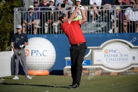 Padraig Harrington, of Ireland, tees off on the first hole as Leo Goosen, left, son of Retief Goosen, watches during the first round of the Father Son Challenge golf tournament, in Orlando, Fla