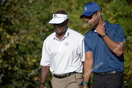 Vijay Singh, left, of Fiji Islands, walks with his son Qass Singh after both hit their tee shots on the first hole during the first round of the Father Son Challenge golf tournament, in Orlando, Fla