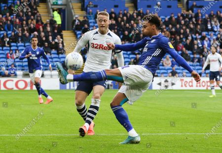Josh Murphy of Cardiff City crosses as Tom Clarke of Preston North End closes in