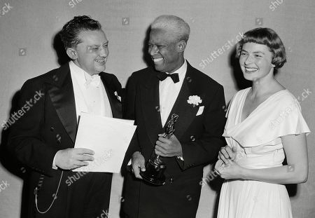 """Stock Image of Jean Hersholt, from left, president of Academy of Motion Pictures Arts and Sciences, congratulates James Baskett, second African American to win an Oscar, for his special award for his portrayal of Uncle Remus in the 1946 Disney feature film """"Song of the South"""" in Los Angeles, Calif. Looking on is Ingrid Bergman, who made presentation to Baskett. Racially segregated movie theaters disappeared decades ago after court rulings struck down the legal framework of Jim Crow America, but another element of the era just won't die: Walt Disney's 1946 movie """"Song of the South."""" The company didn't include the film in its new Disney Plus streaming service"""