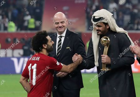 FIFA president Gianni Infantino, center, watches as Sheikh Joaan bin Hamad bin Khalifa Al Thani, right, shake hands with Liverpool's Mohamed Salah, left, during the Club World Cup final soccer match between Liverpool and Flamengo at Khalifa International Stadium in Doha, Qatar