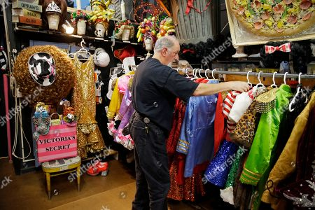 """Stage manager John Camajani looks through the numerous costumes hanging in the backstage dressing room of the musical """"Beach Blanket Babylon"""" in San Francisco. The campy small San Francisco show that's been a must-see for tourists and locals alike for more than 45 years, making it the nation's longest continuously running musical revue, is closing its curtain. Its final performance is set for New Year's Eve"""