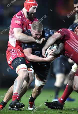 Ross Moriarty of Dragons is tackled by Blade Thomson and Ken Owens of Scarlets.