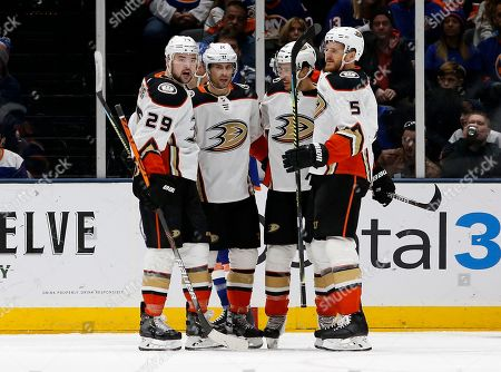 Anaheim Ducks center Adam Henrique (14) celebrates his goal against the New York Islanders with teammates Devin Shore (29), Michael Del Zotto (44) and Korbinian Holzer (5) during the second period of an NHL hockey game, in Uniondale, N.Y