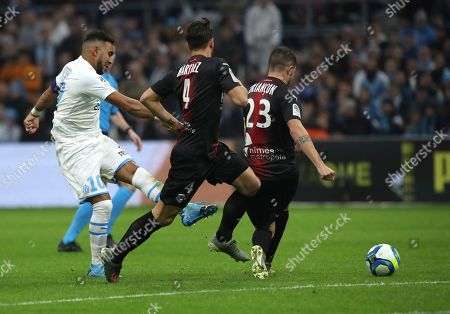 Marseille's Dimitri Payet, left, makes an attempt to score during the French League One soccer match between Marseille and Nimes at the Velodrome stadium in Marseille, southern France