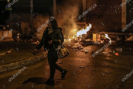A woman pass by burn Waste dump and car tires where supporters of Outgoing Prime Minister Saad Hariri who close the road during a protest against the newly appointed Lebanese Prime Minister Hassan Diab, at  Al-Barbir neighborhood in Beirut, Lebanon, 21 December 2019 . Lebanon's premier designate Hassan Diab vowed on 19 December to form a government of experts. However, Sunni protesters blocked roads with burning car tires to protest the appointment of Diab, who has the support of Shiite group Hezbollah.