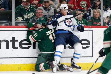 Stock Photo of Winnipeg Jets left wing Gabriel Bourque (57) checks Minnesota Wild center Luke Johnson into the boards in the second period of an NHL hockey game, in St. Paul, Minn. The Jets defeated the Wild 6-0