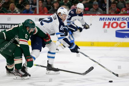 Stock Image of Winnipeg Jets center Mason Appleton (82) is pressured by Minnesota Wild left wing Zach Parise (11) in the second period of an NHL hockey game, in St. Paul, Minn. The Jets defeated the Wild 6-0