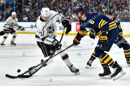 Los Angeles Kings right wing Tyler Toffoli, left, has the puck tipped away by Buffalo Sabres defenseman Marco Scandella during the first period of an NHL hockey game in Buffalo, N.Y., . Buffalo beat Los Angeles 3-2