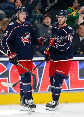 Columbus Blue Jackets' Zach Werenski, left, celebrates his goal against the New Jersey Devils with teammate Alexander Wennberg, of Sweden, during the third period of an NHL hockey game, in Columbus, Ohio. The Blue Jackets beat the Devils 5-1