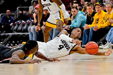 Cincinnati guard Keith Williams, left, fights for a loose ball with Iowa guard Bakari Evelyn (4) during the second half of an NCAA college basketball game, in Chicago