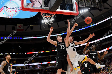 Iowa guard Joe Wieskamp (10) and Cincinnati center Chris Vogt (33) and guard Keith Williams (2) look for a rebound during the first half of an NCAA college basketball game, in Chicago