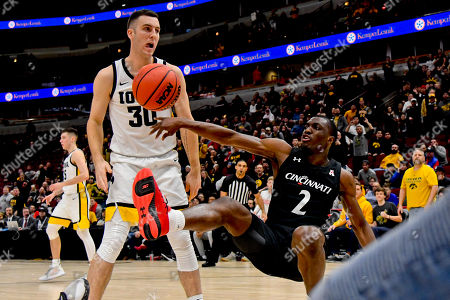 Cincinnati guard Keith Williams (2) tries to keep the ball in play, near Iowa guard Connor McCaffery (30) during the second half of an NCAA college basketball game, in Chicago