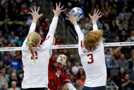Wisconsin's Dana Rettke (16) this a spike blocked by Stanford's Holly Campbell (3) and Kate Formico (11) during the NCAA Division I women's volleyball championship match, in Pittsburgh