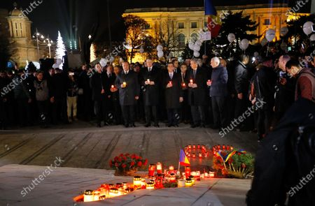 Stock Photo of Romanian President Klaus Iohannis (C) and Romanian Prime Minister Ludovic Orban (C-R), accompanied by other high ranked officials, pay respect for the 1989 heroes while holding burning candles, as human rights activists hold helium-filled balloons, labeled with the word 'FREEDOM', during a commemoration rally dedicated to those who died during the 1989 popular uprising, marking the 30th anniversary, in Bucharest, Romania, 22 December 2019. Romanians pay their respect to the activists, who in 1989 took to the streets in the civil unrest that toppled Eastern Europe's most repressive communist regime. More than 1,100 people were killed across Romania during clashes between demonstrators and forces loyal to then dictator Nicolae Ceausescu.
