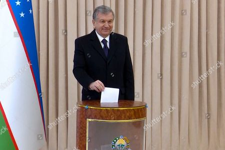 In this handout screengrab provided by the UZREPORT Government TV Channel, Uzbekistan's President Shavkat Mirziyoyev poses for a photo during the parliamentary elections at at a polling station in Tashkent, Uzbekistan, . Uzbeks head to the polls to vote in parliamentary elections on Sunday, Dec. 22, 2019, for the first time since Shavkat Mirziyoev has been president following the death of long-time leader Islam Karimov