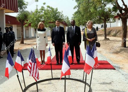 French President Emmanuel Macron, second left, and his wife Brigitte Macron, left, with Ivory Coast President Alassane Ouattara, second right, and his wife Dominique pay homage to the French and U.S. soldiers killed in 2004, as they visit the city of Bouake, Ivory Coast, . Macron has vowed to boost the fight against Islamic extremism in West Africa where French troops killed 33 Islamic extremists in central Mali. Macron made the announcement Saturday on his second day in Ivory Coast, where he met with Ivorian President Alassane Ouattara in Abidjan