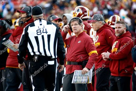 Washington Redskins interim head coach Bill Callahan, center, talks with line judge Mark Steinkerchner (84) during the first half of an NFL football game against the New York Giants, in Landover, Md