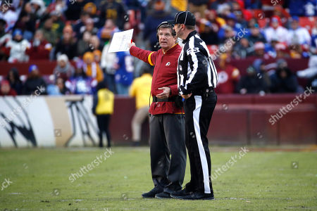 Washington Redskins interim head coach Bill Callahan, left, talks with side judge Bob Waggoner (25) during the first half of an NFL football game against the New York Giants, in Landover, Md