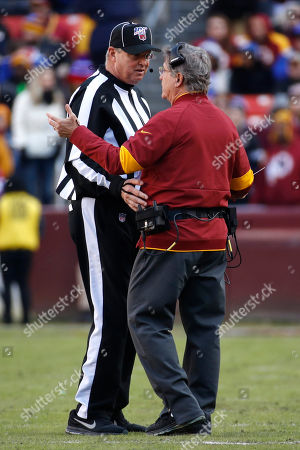 Washington Redskins interim head coach Bill Callahan, right, talks with line judge Mark Steinkerchner during the first half of an NFL football game against the New York Giants, in Landover, Md
