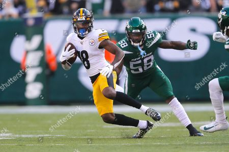 Pittsburgh Steelers wide receiver Diontae Johnson (18) runs with the ball in front of New York Jets outside linebacker James Burgess (58) in the first half of an NFL football game, in East Rutherford, N.J