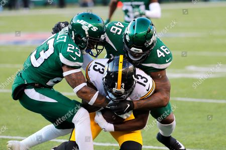 Pittsburgh Steelers wide receiver James Washington (13) runs with the ball as New York Jets cornerback Arthur Maulet (23) and New York Jets linebacker Neville Hewitt (46) try to stop him in the second half of an NFL football game, in East Rutherford, N.J