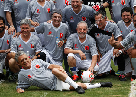 Brazil's former president Luiz Inacio Lula da Silva, center, and the singer Chico Buarque, bottom left, pose for a photo prior to a friendly soccer match with members of the Landless Workers Movement in Guararema, Brazil