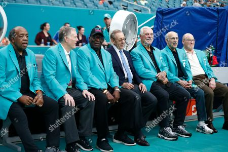 Miami Dolphins owner Stephen Ross sits with the 1972 Miami Dolphins perfect team players, during the first half at an NFL football game against the Cincinnati Bengals, in Miami Gardens, Fla