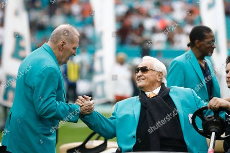 Former Miami Dolphins head coach Don Shula is greeted on the field by former players during half time at an NFL football game against the Cincinnati Bengals, in Miami Gardens, Fla. The 1972 undefeated team was celebrated on the field