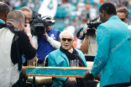 Former Miami Dolphins head coach Don Shula looks at a large cake celebrating the 1972 undefeated season and his birthday, during the half time at an NFL football game against the Cincinnati Bengals, in Miami Gardens, Fla