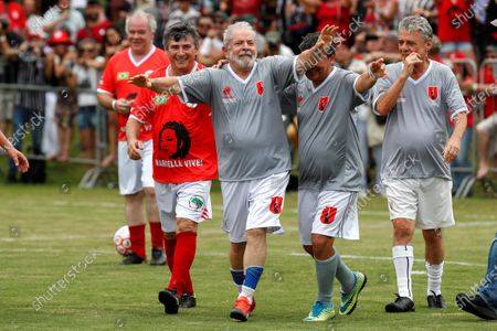 Stock Photo of Former Brazilian President Luiz Inacio Lula da Silva (C) celebrates after scoring next to Brazilian musician Chico Buarque (R) during a friendly soccer match as part of Christmas and New Years celebrations, at the school Florestan Fernandes, in Guararema, Brazil, 22 December 2019.