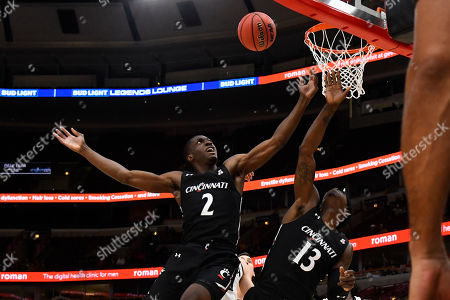 Keith Williams, Tre Scott. Cincinnati guard Keith Williams (2) and Cincinnati Bearcats forward Tre Scott (13) fight for a rebound against Iowa in the first half of an NCAA college basketball game, in Chicago