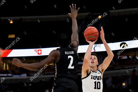 Joe Wieskamp, Keith Williams. Iowa guard Joe Wieskamp (10) shoots against Cincinnati guard Keith Williams (2) in the first half of an NCAA college basketball game, in Chicago