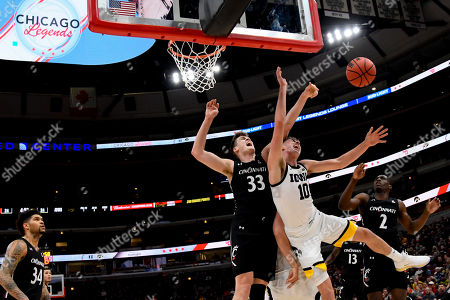 Joe Wieskamp, Chris Vogt, Keith Williams. Iowa guard Joe Wieskamp (10) chases a rebound against Cincinnati center Chris Vogt (33) and guard Keith Williams (2) in the first half of an NCAA college basketball game, in Chicago
