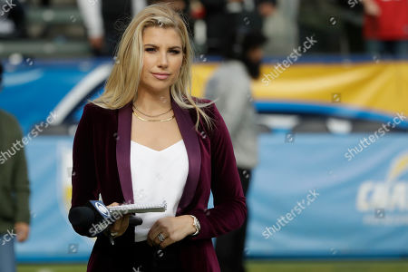 Melanie Collins CBS sideline reporter watches during warm ups before an NFL football game between the Los Angeles Chargers and the Oakland Raiders, in Carson, Calif
