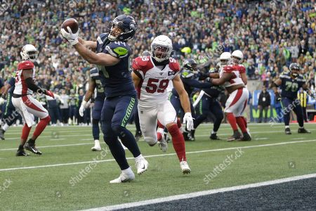 Seattle Seahawks fullback Nick Bellore (44) is catches a pass for a touchdown ahead of Arizona Cardinals linebacker Joe Walker (59) to score a touchdown during the first half of an NFL football game, in Seattle