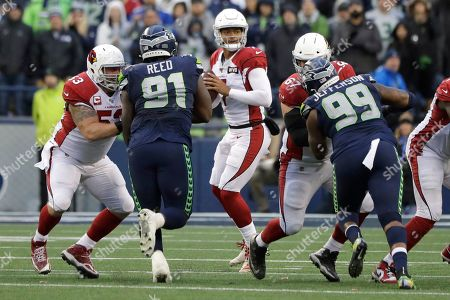 Arizona Cardinals quarterback Brett Hundley, center, drops to pass against the Seattle Seahawks during the second half of an NFL football game, in Seattle