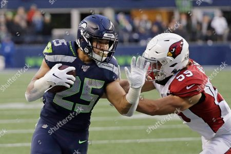 Seattle Seahawks running back Travis Homer, left, rushes against Arizona Cardinals linebacker Joe Walker, right, during the second half of an NFL football game, in Seattle