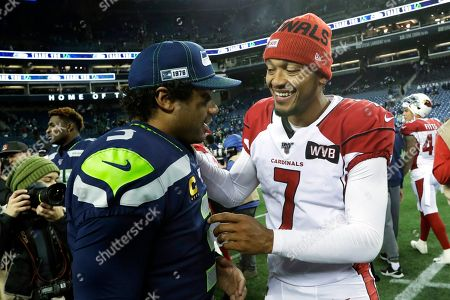 Arizona Cardinals backup quarterback Brett Hundley (7) talks with Seattle Seahawks quarterback Russell Wilson, left, following an NFL football game, in Seattle. Hundley stepped in during the second quarter after starting quarterback Kyler Murray left with an injury and the Cardinals won 27-13