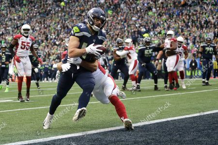 Seattle Seahawks fullback Nick Bellore (44) is tackled by Arizona Cardinals linebacker Joe Walker as he scores a touchdown during the first half of an NFL football game, in Seattle