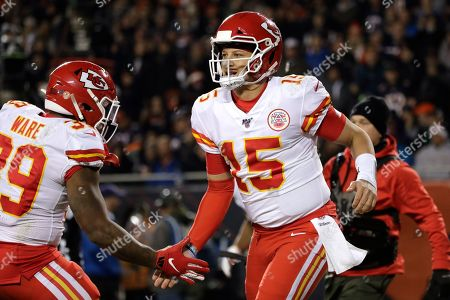 Kansas City Chiefs quarterback Patrick Mahomes (15) celebrates his 12-yard touchdown run with running back Spencer Ware in the first half of an NFL football game against the Chicago Bears in Chicago