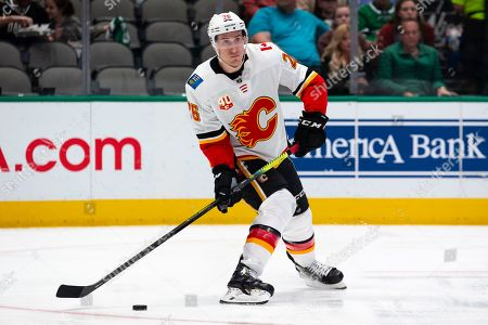 Calgary Flames defenseman Michael Stone (26) looks to pass the puck during the first period of an NHL hockey game against the Dallas Stars, in Dallas